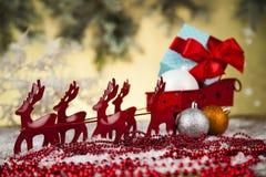在礼物盒背景的圣诞老人雪橇 免版税库存图片