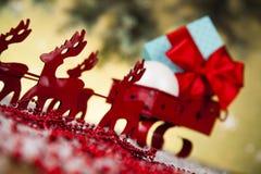 在礼物盒背景的圣诞老人雪橇 图库摄影