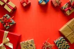 在礼物纸包裹的圣诞节礼物的顶视图装饰用在红色纸背景的丝带 库存图片