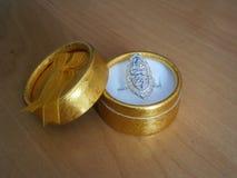 在礼物金黄箱子的银色圆环 库存照片