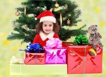 在礼物围拢的圣诞树附近的小女孩 免版税图库摄影