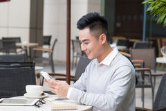 在社会媒介应用的年轻亚洲愉快的人正文消息由智能手机在咖啡馆的咖啡时间,偶然生活方式总之 免版税库存照片