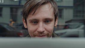 在社会网络的微笑的白种人人重写与他的朋友通过便携式计算机,当休息在面包店商店时 股票录像