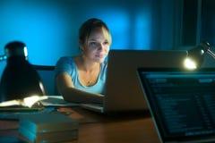 在社会网络的妇女文字与后个人计算机在晚上 免版税库存照片