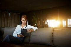 在社会网络的迷人的女实业家读书femenine博克通过触摸板,当在现代咖啡店时的等待的菜单, 库存照片