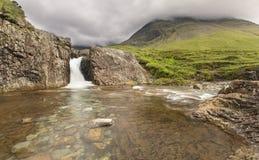 在神仙的瀑布合并在斯凯岛小岛的岩石小河  图库摄影