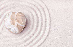 在禅宗庭院的美好的沙子的一块混杂的海滩石头 库存照片