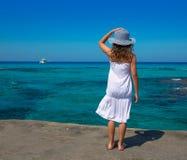 在福门特拉岛伊维萨岛海滩绿松石的女孩背面图 图库摄影