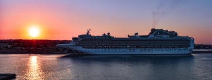 在离开前的片刻与在享受金黄小时天空的罗得岛口岸的轮渡在日落期间 免版税库存图片