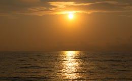 在离开在距离的海的明亮的橙色日落 图库摄影