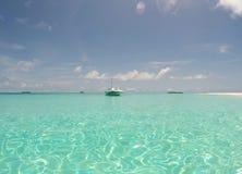 在离开的天堂海岛岸的小船  库存照片