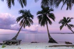 在离开的热带海滩的桃红色黄昏在印度尼西亚 免版税库存图片