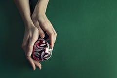 在秀丽手上holded的圣诞节球 免版税库存图片