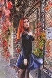 在秋叶之前围拢的门前面的高红色顶头哥特式妇女 免版税图库摄影