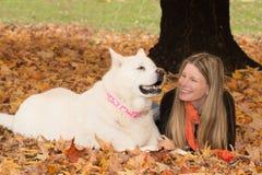 在秋叶的微笑的白肤金发的妇女和白色狗 库存图片