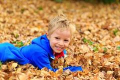 在秋叶的愉快的小男孩乐趣 库存照片