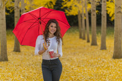 在秋叶的深色的模型与伞和饮料 库存图片
