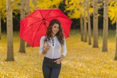 在秋叶的深色的模型与伞 免版税库存图片
