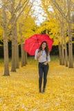 在秋叶的深色的模型与伞 图库摄影