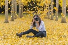 在秋叶的深色的模型与DSLR照相机 图库摄影