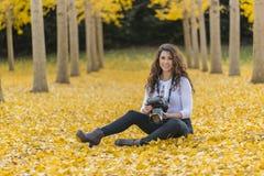 在秋叶的深色的模型与DSLR照相机 库存照片