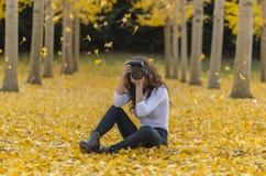 在秋叶的深色的模型与DSLR照相机 免版税库存图片