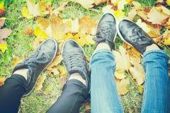 在秋叶,顶视图,被定调子的照片的两双女孩鞋子 免版税图库摄影