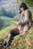 读在秋天光的端庄的妇女一本书 免版税库存照片