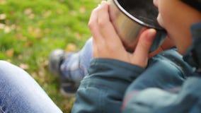 在秋天公园人坐草坪和饮料热的茶,在新鲜空气的步行 接近的现有量 股票录像
