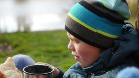 在秋天公园人坐草坪和饮料热的茶,在新鲜空气的步行 特写镜头 影视素材
