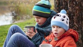 在秋天公园孩子坐草坪和饮料热的茶,在新鲜空气的步行 股票录像