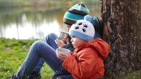 在秋天公园孩子坐草坪和饮料热的茶,在新鲜空气的步行 影视素材