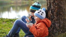 在秋天公园孩子坐草坪和饮料热的茶,在新鲜空气的步行 库存图片