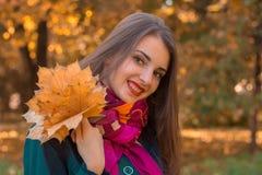 在秋天公园微笑和在她的手上的迷人的女孩拿着枫叶 免版税库存照片