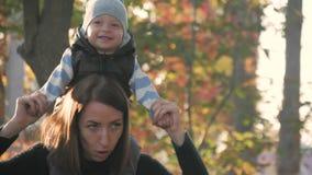 在秋天公园照顾盘旋一个小儿子 秋天系列愉快的公园 在自然概念的愉快的家庭在慢 股票录像