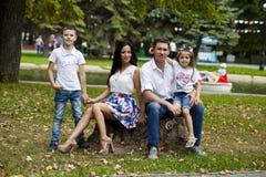 在秋天公园的背景的年轻愉快的家庭画象 库存图片
