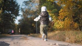 在秋天公园里跑步的快乐男孩 小孩在秋日散步 金叶秋叶林 股票录像