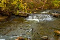 在秋天叶子下的微小的瀑布 库存照片