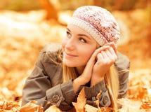 在秋天叶子的逗人喜爱的女性位置 免版税库存照片