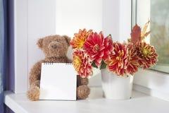 在秋天大丽花旁边花束的女用连杉衬裤熊  女用连杉衬裤熊拿着写的一个笔记薄 免版税库存图片
