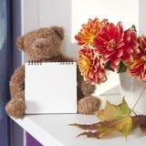 在秋天大丽花旁边花束的女用连杉衬裤熊  女用连杉衬裤熊拿着写的一个笔记薄 图库摄影