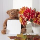 在秋天大丽花旁边花束的女用连杉衬裤熊  女用连杉衬裤熊拿着写的一个笔记薄 免版税图库摄影