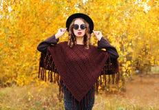 在秋天天塑造少妇佩带的黑帽会议太阳镜和被编织的雨披在黄色叶子 库存图片