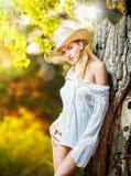 在秋天天塑造有帽子和白色衬衣的画象妇女 免版税图库摄影