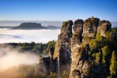 在秋天季节期间的落矶山脉视图 在Bastei,德国的有雾的日出 免版税库存照片