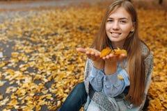 在秋天季节的公园走一个美丽,甜,快乐的女孩的画象 图库摄影