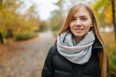 在秋天季节的公园走一个美丽,甜,快乐的女孩的画象 免版税库存照片