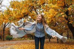 在秋天季节的公园走一个美丽,甜,快乐的女孩的画象 免版税库存图片