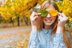 在秋天季节的公园走一个美丽,甜,快乐的女孩的画象 免版税图库摄影