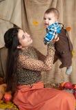 在秋天季节的家庭画象 妇女和小男孩坐黄色秋天叶子、苹果、南瓜和装饰 库存图片